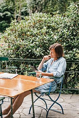 Woman with e-book on terrace - p586m1184903 by Kniel Synnatzschke