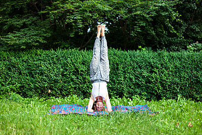 Young woman practicing yoga in park - p795m2199809 by JanJasperKlein