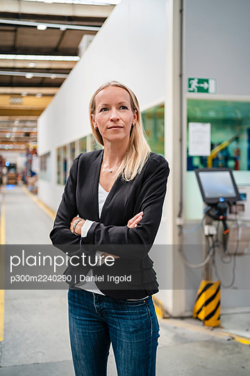 Confident blond female entrepreneur with arms crossed standing in industry - p300m2240290 von Daniel Ingold