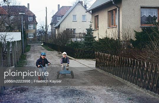 Deutschland, Kinder spielen auf der Straße vor Häusern in der DDR - p986m2223998 von Friedrich Kayser
