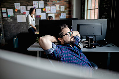 Thoughtful creative businessman looking away in office - p1192m2040400 by Hero Images