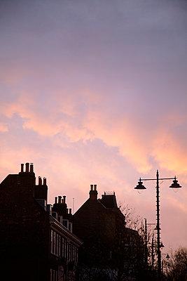 Silhouetten von Hausdächern vor Abendhimmel - p1248m2228864 von miguel sobreira