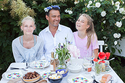 Father with daughters at table in garden - p312m1472611 by Christina Strehlow