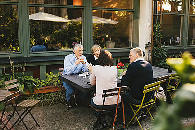 Senior male and female friends having talking at outdoor restaurant - p426m1143268 by Maskot