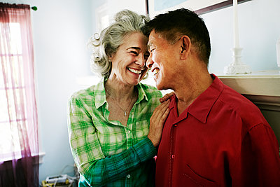 Smiling couple hugging in living room - p555m1410206 by Peathegee Inc