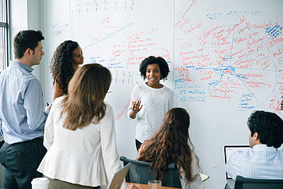 Businesswoman talking near whiteboard in meeting - p555m1504094 by John Fedele