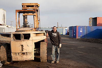 Man on construction site standing by heavy machinery - p924m1422753 by Raphye Alexius