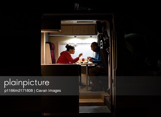 Couple having a relaxed dinner in a motorhome during a trip. - p1166m2171808 by Cavan Images
