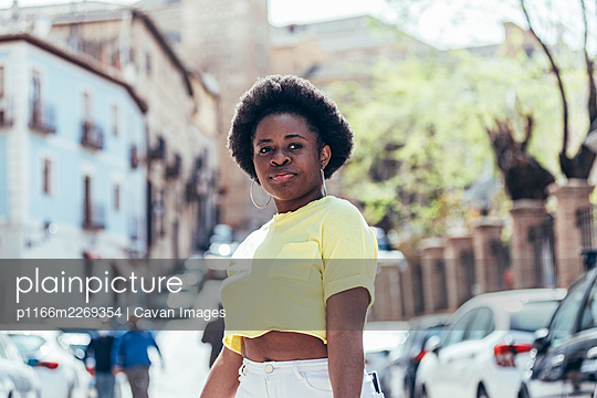 Portrait of black girl with afro hair on a city street. - p1166m2269354 by Cavan Images