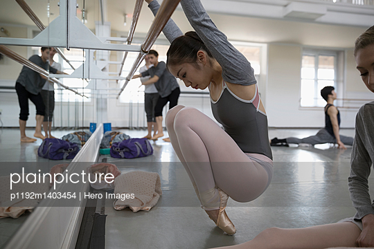 Female ballet dancer stretching, warming up at barre in dace studio