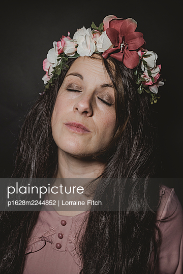 Dark haired woman with floral wreath in her hair - p1628m2244852 by Lorraine Fitch