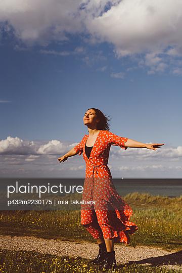 Frau genießt den Wind am Meer - p432m2230175 von mia takahara