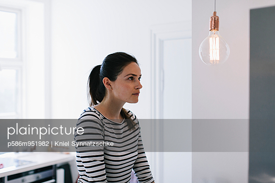 Junge Frau im gestreiften Kleid blickt auf eine Glühbirne - p586m951982 von Kniel Synnatzschke