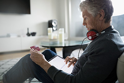 Senior man with headphones online shopping with digital tablet and credit card - p1192m1517051 by Hero Images