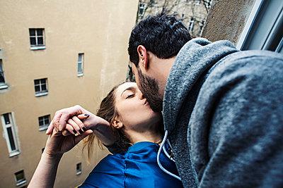 Junges Paar lehnt sich aus einem Fenster und küsst sich  - p1301m1424728 von Delia Baum