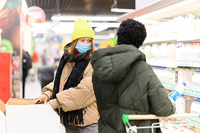 Female friends in warm clothing buying groceries at supermarket during COVID-19 - p300m2282592 by Katharina und Ekaterina
