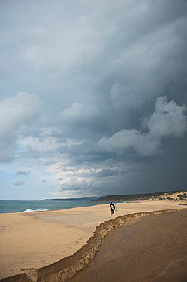 Man walking on sand with his surfboard on stormy day - p3071230f by Enrico  Calderoni