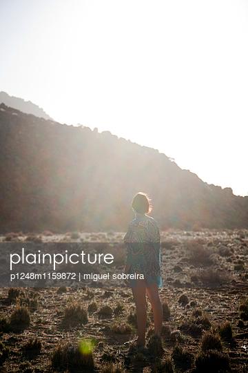 Frau steht in Wüstenlandschaft - p1248m1159872 von miguel sobreira