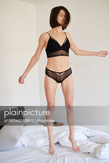 Young brunette woman jumping in her bed at morning - p1607m2183915 by zhushman