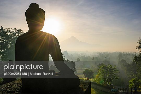 Indonesia, Java, Borobudur Temple Complex, sitting Buddha in backlight - p300m2081188 by Michael Runkel