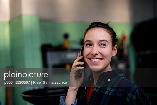 Female mechanic smiling while talking on mobile phone at workshop - p300m2290597 by Kniel Synnatzschke