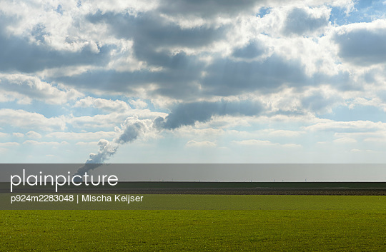 Netherlands, Zeeland, Rilland, Field with cooling tower in distance - p924m2283048 by Mischa Keijser
