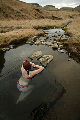 Woman relaxing in a natural hot pool - p1028m755013 by Jean Marmeisse