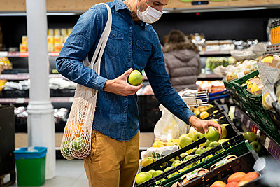 Midsection of man wearing face mask buying granny smith apples in supermarket - p300m2242282 by VITTA GALLERY
