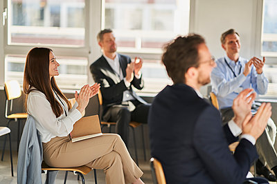 Businesswoman clapping hands with colleagues in education conference centre - p300m2281423 by Annika List
