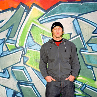 portrait of young man leaning on graffiti covered wall - p3162516f by Kalle Singer