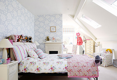 Contrasting floral patterns in teenage girl's bedroom attic conversion in Harrogate home - p349m790389 by Brent Darby