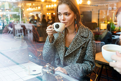 Young woman drinking coffee with friend in cafe, London, UK - p429m2075294 by Tamboly