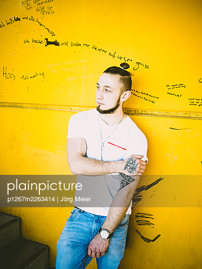 Man with tattoo and pigtail against yellow wall - p1267m2263414 by Jörg Meier