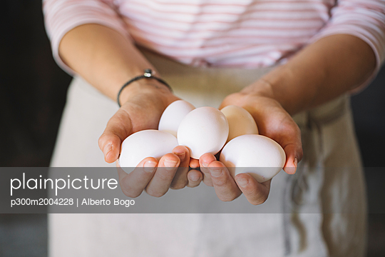 Woman holding raw white eggs - p300m2004228 von Alberto Bogo