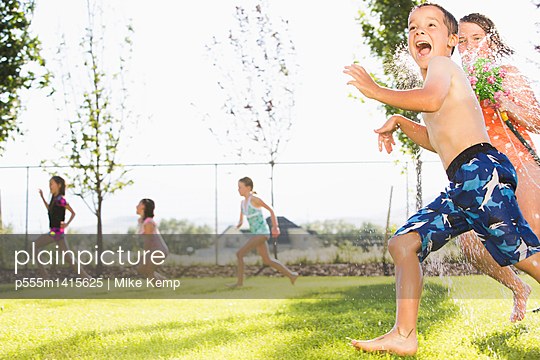 Caucasian children playing in sprinkler in backyard - p555m1415625 by Mike Kemp