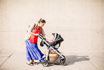 Side view of mom who stop in street to take care of baby in stroller - p1166m2078478 by Cavan Images