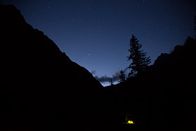 Illuminated tent, surrounded by high mountains - p1682m2263428 by Régine Heintz