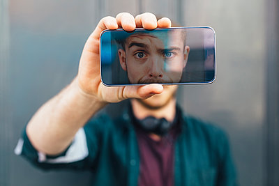 Display of smartphone showing young man pulling funny face - p300m1191469 by Boy photography