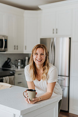 Smiling woman holding mug on kitchen counter while standing at home - p300m2203101 by Sara Monika