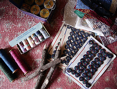 Buttons and vintage bobbins with fabric samples in home of London textiles designer - p349m790433 by Brent Darby