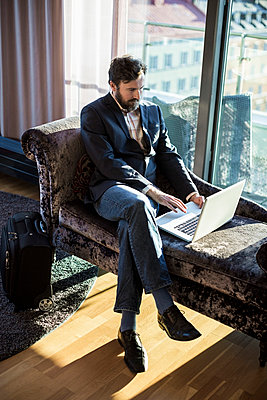 Businessman using laptop in hotel room - p426m920193f by Maskot