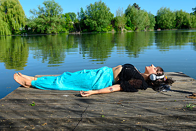 Woman with headphones lying on boardwalk - p427m2203631 by Ralf Mohr