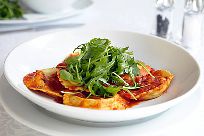 Fresh ravioli with rocket in bowl - p429m1561613 by Debby Lewis-Harrison