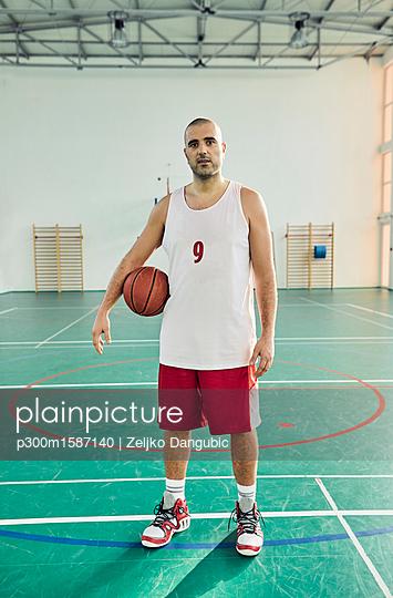 Man with basketball, indoor - p300m1587140 von Zeljko Dangubic