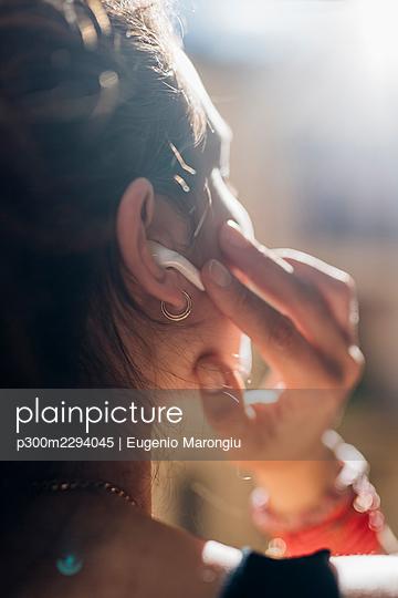 Woman touching wireless in-ear headphones - p300m2294045 by Eugenio Marongiu