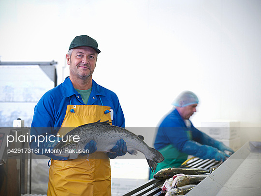 Fishmonger holding catch of the day - p42917316f by Monty Rakusen