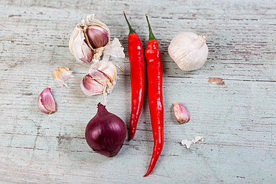 Red chili pods, red onion and garlic on wood - p300m1228618 by JLPfeifer