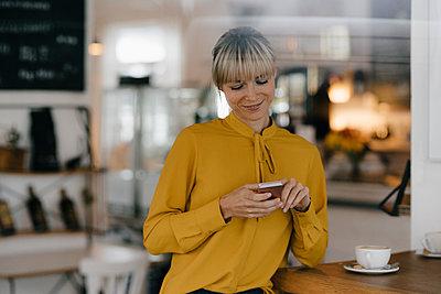 Blond businesswoman using smartphone in a coffee shop, reading text messages - p300m2103646 von Joseffson