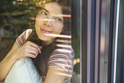 Portrait of smiling young woman behind windowpane - p300m2104450 by Uwe Umstätter