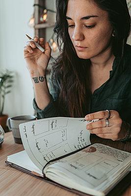 Woman checking her diary - p312m2191296 by Rania Rönntoft